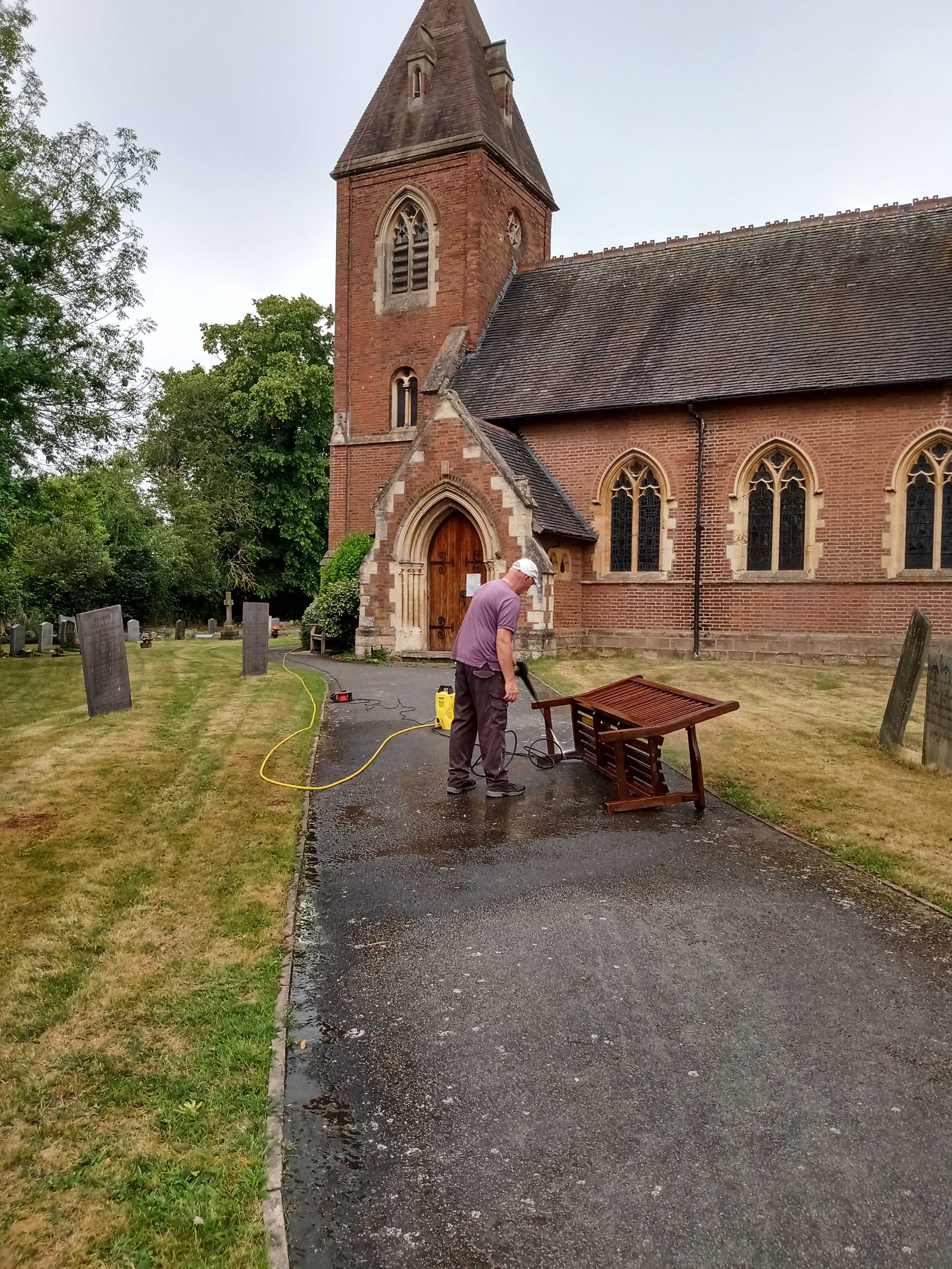 Steve power washing church benches.