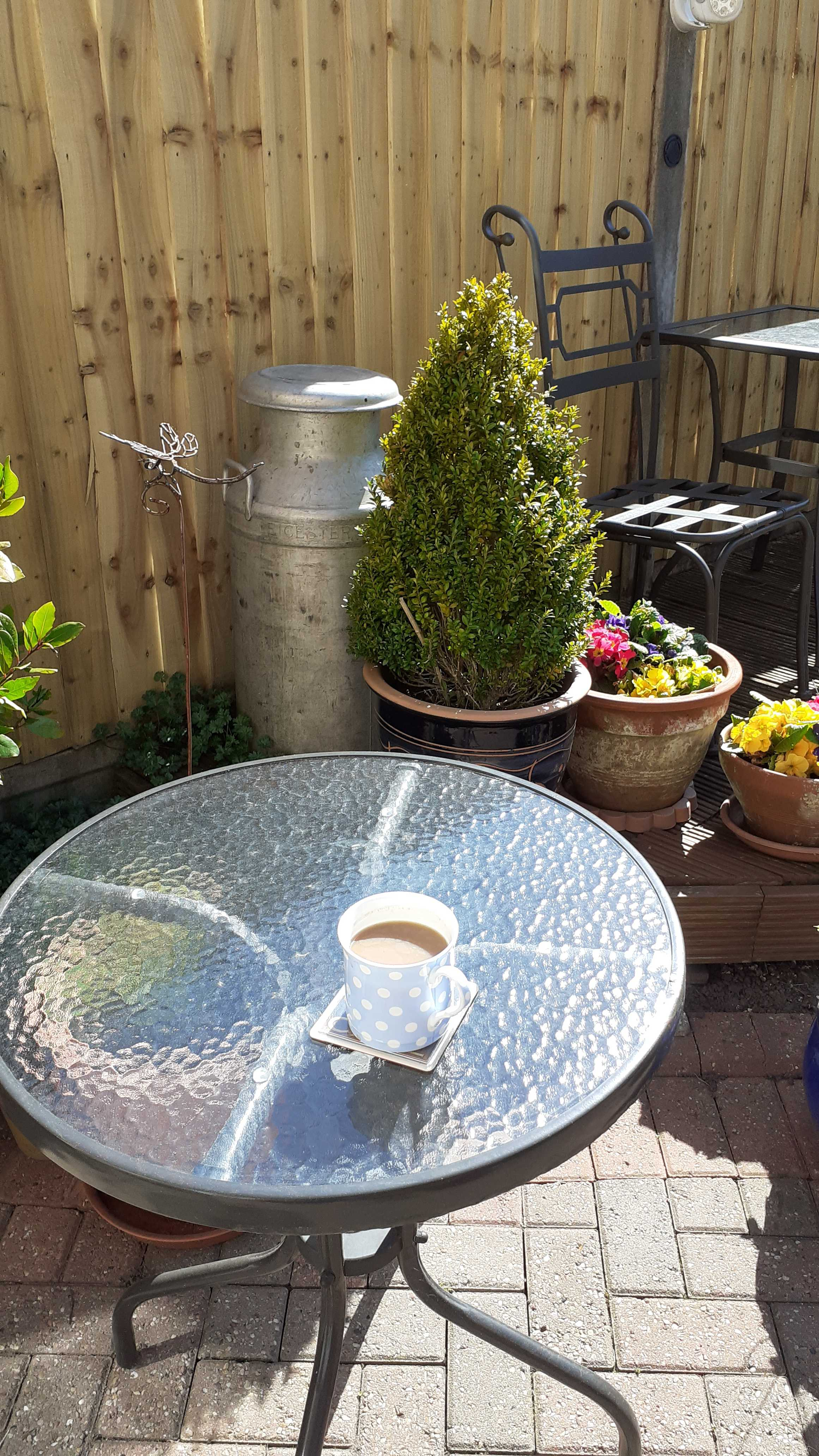 A small round garden table with a cuppa on it, in a garden setting.